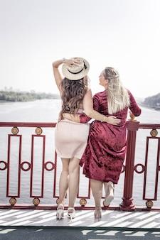 Близко к природе. счастливые женщины в восторге, наслаждаясь прекрасным видом, стоя на мосту