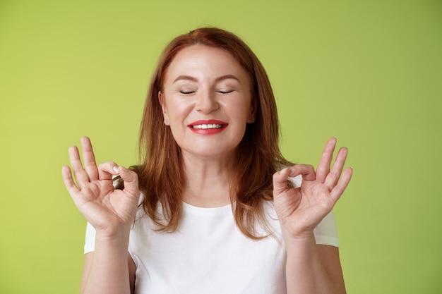 완벽에 가까운 근접 촬영 평화로운 편안한 빨간 머리 행복한 여자 눈을 감고 순수 기쁘게 미소 쇼 선 평화 만족 제스처 명상 도달 너바나 진정 스탠드 녹색 벽
