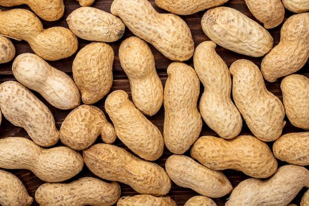 Закрыть вид сверху арахиса в скорлупе на деревянном столе