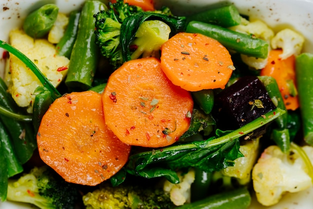 Close top view stewed vegetables carrots asparagus with broccoli in a plate