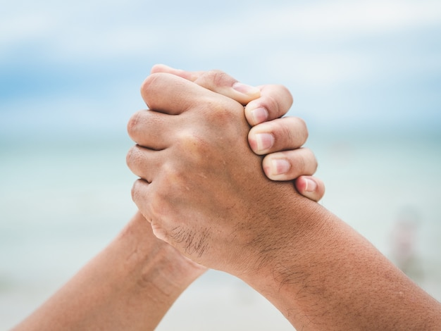 Close two holding hands on sea bokeh background