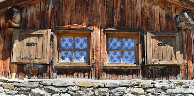 Close on two little window on a facade of a mountain chalet