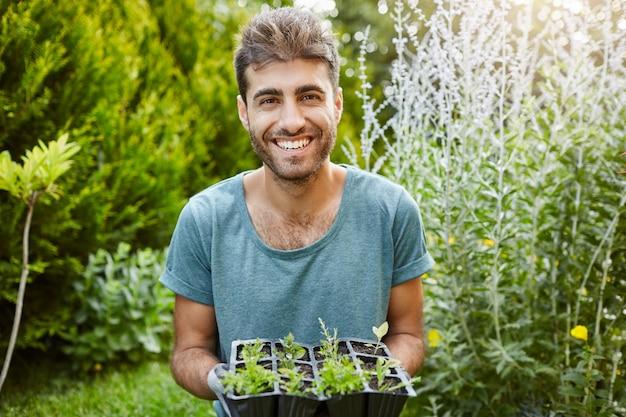 Close u outdoors portrait of beautiful joyful hispanic man in blue shirt smiling with teeth, holding pot with microgreens, working in garden.
