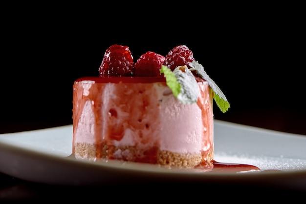 Close-uf восхитительный десерт суфле, украшенный малиной и свежими листьями мяты, подается на белой квадратной тарелке. фотография сделана на черной стене. вкусный для сладкого шведского стола или общественного питания.