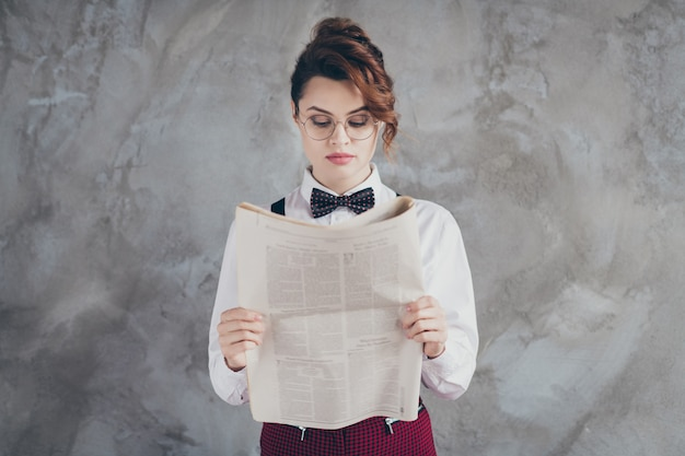 Close-uo portrait of her she nice-looking attractive lovely pretty bossy authoritative focused wavy-haired girl financier reading finance periodic isolated on gray concrete industrial wall background