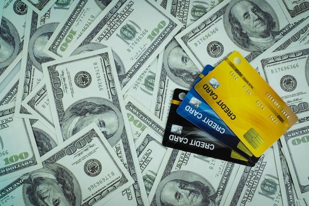 돈 지폐 100 usd 배경 더미에서 격리된 3개의 신용 카드를 닫습니다