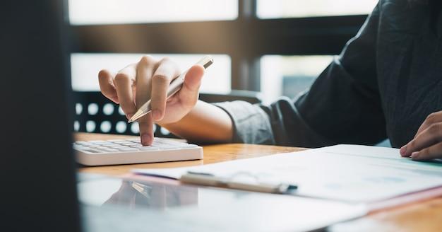 Закройте счет, работающий о финансовом с калькулятором в офисе для расчета расходов, концепции бухгалтерского учета.