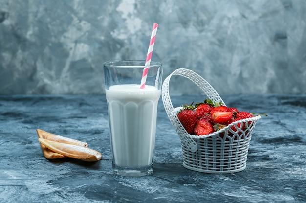 濃い青と灰色の大理石の背景に牛乳とココナッツのスライスの水差しとイチゴのバスケットをクローズアップ。水平