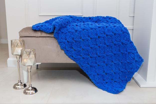 クローズアップ、美しい青いニットのぬいぐるみのウールの毛布が、暖かく居心地の良いコンセプトの燭台と一緒にソファの上に置かれています。