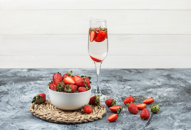 근접 어두운 파란색 대리석 및 흰색 나무 보드 표면에 음료 한 잔 함께 둥근 고리 버들 세공 플레이스 매트에 딸기 한 그릇. 수평