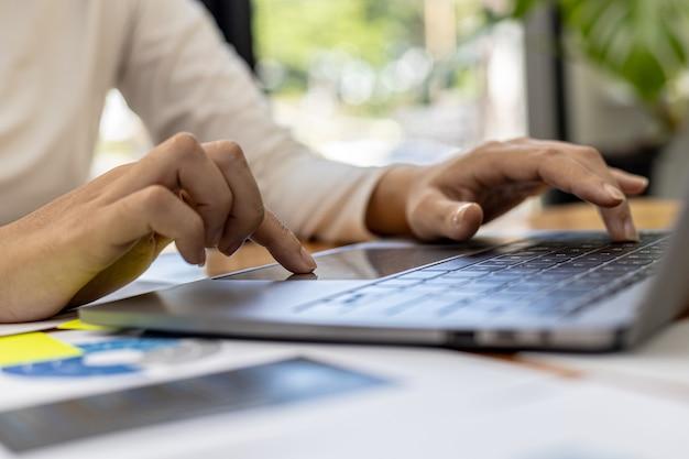 클로즈업 개인실에서 일하는 비즈니스 여성, 그녀는 노트북 키보드로 타이핑을 하고 있으며 메신저를 사용하여 파트너와 채팅합니다. 통신에 기술을 사용하는 개념.