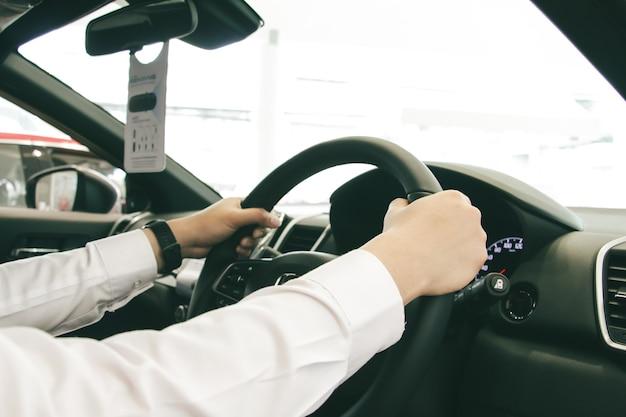 근접 사업가 손에 빨간색 콘솔 스티어링 휠을 들고 시계를 넣어. 운전 자동차 개념입니다. 안전 운전 개념입니다.