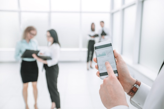 확대. 사업가는 스마트폰을 사용하여 재무 데이터를 확인합니다. 복사 공간이 있는 사진