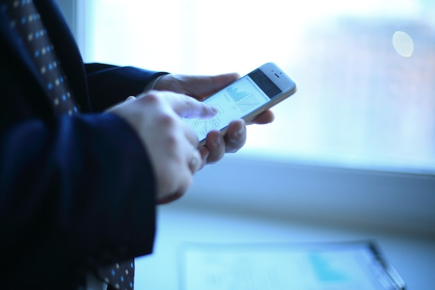 확대. 사업가는 사무실의 작업 테이블 근처에 서 있는 동안 스마트폰을 사용합니다.사진 복사 공간