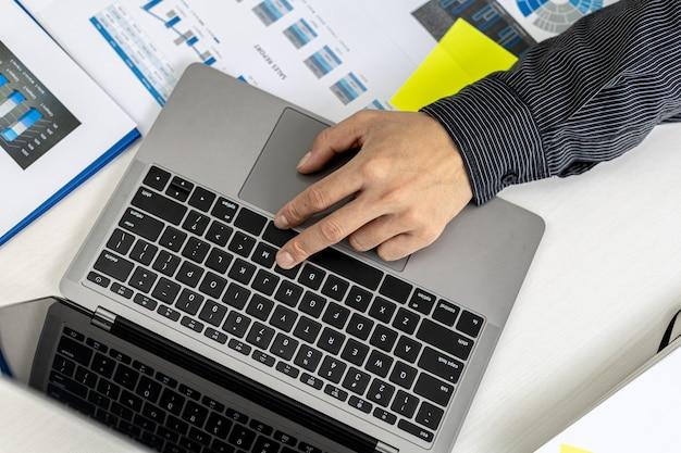 클로즈업 개인실에서 일하는 사업가가 노트북 키보드를 입력하고 메신저를 사용하여 파트너와 채팅합니다. 통신에 기술을 사용하는 개념.