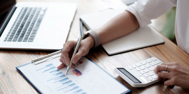 クローズアップ実業家は、財務チャートレポートを作成し、ビジネスコストと利益を計算し、自分の机に座っています。