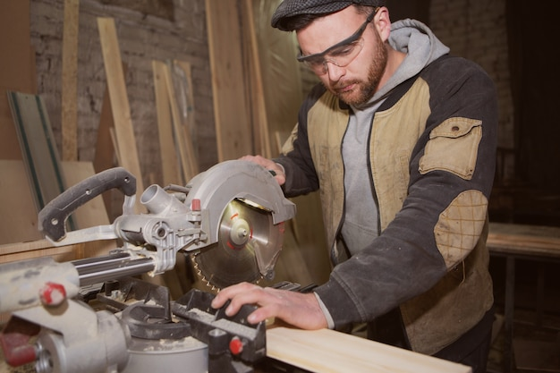 大工仕事で木工をしている作業服を着た大工を閉じます。ワークショップで丸鋸で木の板を切った小さなビジネスオーナー