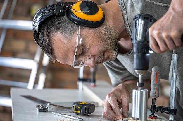 Закройте плотника, работающего с деревом и строительными инструментами в доме