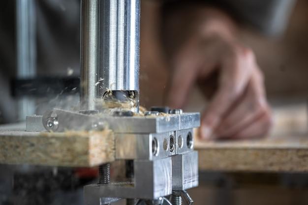 Закройте плотника, работающего с деревом и строительными инструментами в доме.