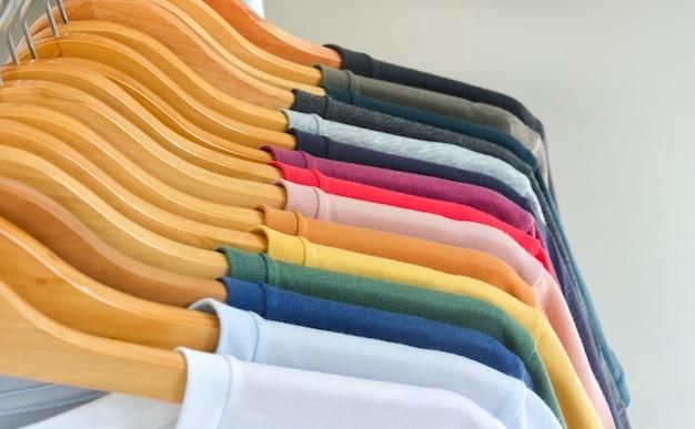 Закройте коллекцию цветных футболок, висящих на деревянной вешалке для одежды на белом фоне