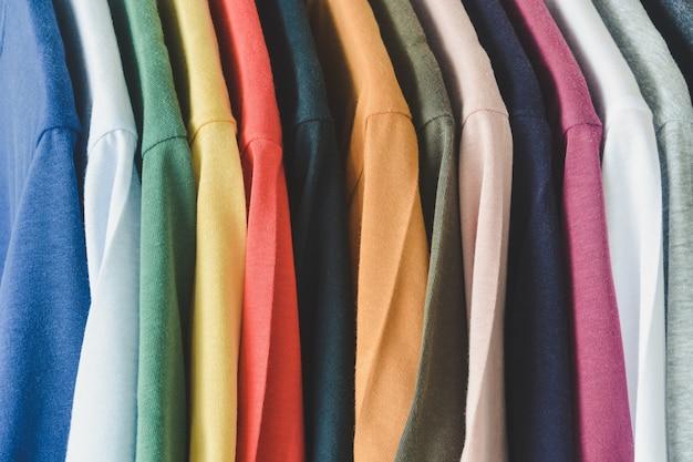 Закройте коллекцию разноцветных футболок, висящих на вешалке в шкафу или вешалке для одежды