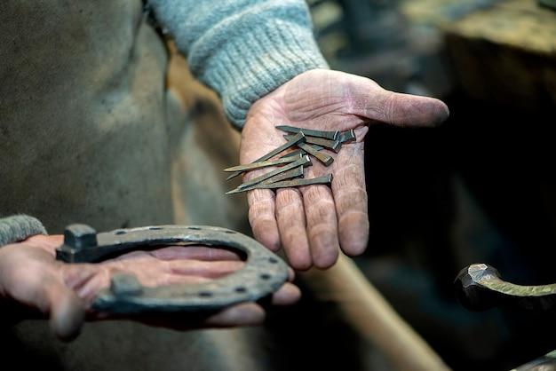 汚れた鍛冶屋の手が馬の蹄鉄と釘を持っているクローズアップ