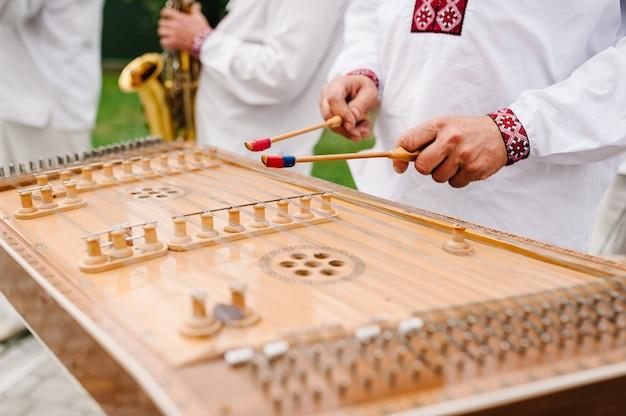 Крупным планом цимбалы, традиционный тайский музыкальный инструмент. мужчина играет на забитых цимбалах с молотками. свадебный музыкант.