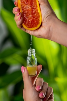 Крупный план: женская рука вдавливает грейпфрутовый сок в стеклянную бутылку