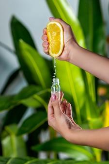 Крупный план: женская рука сжимает сок из лимона в стеклянную бутылку. натуральная косметика