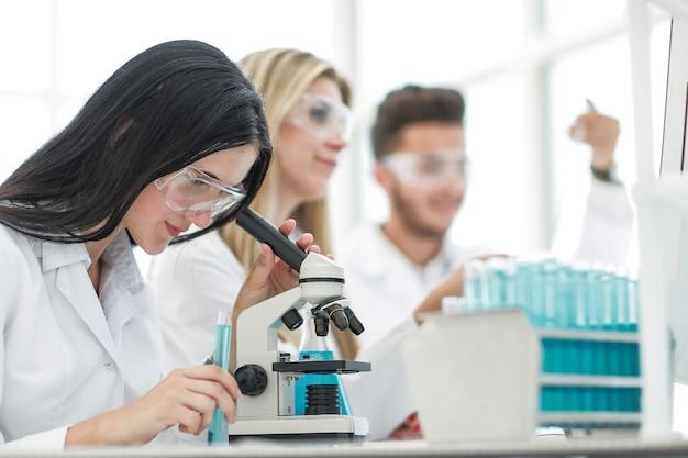 閉じる。女性の科学者は、実験室での研究に顕微鏡を使用しています