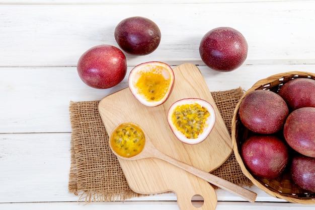 白い木製のテーブル表面に新鮮なパッションフルーツを閉じる