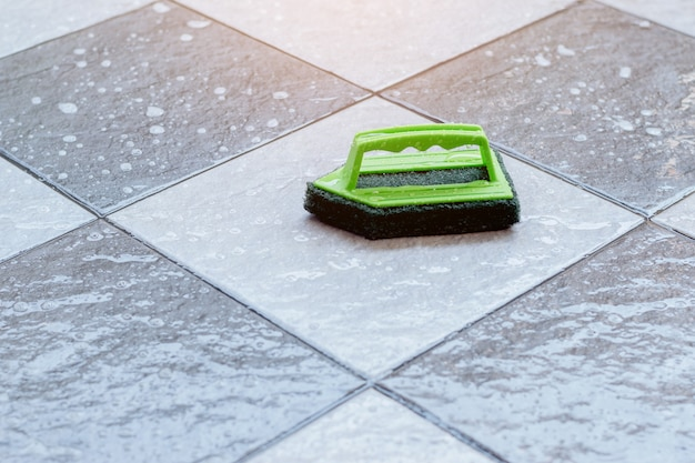 젖은 타일 바닥에 놓인 바닥을 문지르고 청소하기 위해 녹색 플라스틱 브러시를 닫습니다.