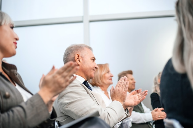 閉じる。ビジネスセミナー中にビジネスマンのグループが拍手喝采します。ビジネスと教育