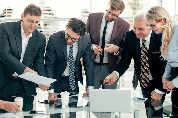 閉じる。興味を持ってノートパソコンの画面を見ている従業員のグループ
