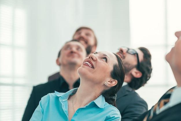 閉じる。見上げる成功した起業家のグループ。スペースのコピー付きの写真