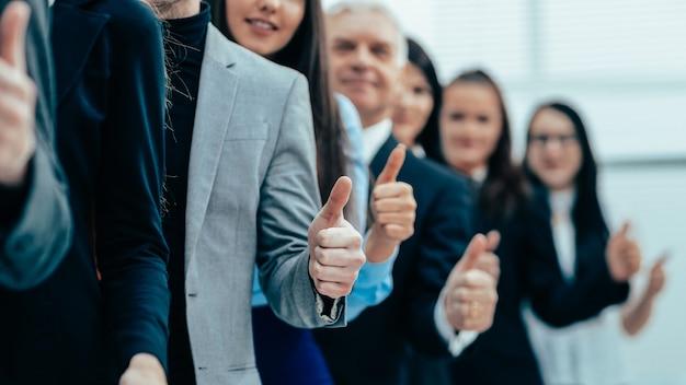 Закройте вверх. группа молодых предпринимателей, стоящих вместе и поднимающих вверх большие пальцы руки
