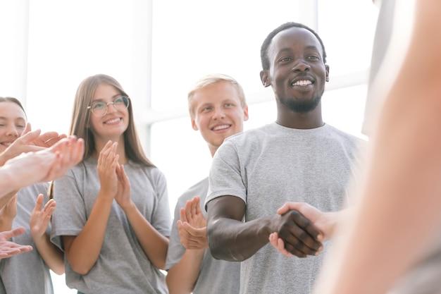 Закройте вверх. группа молодых людей встречает выступающего аплодисментами. бизнес и образование
