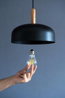 확대. 손이 멋진 로프트 램프로 전구를 바꿉니다. 나선형 필라멘트 램프. 현대적인 인테리어 장식.