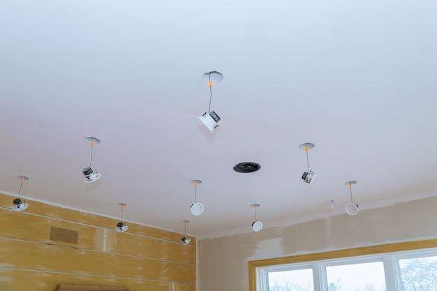 Крупным планом рука меняет световой светодиод в стильной заготовке для установки внутреннего освещения на потолке.