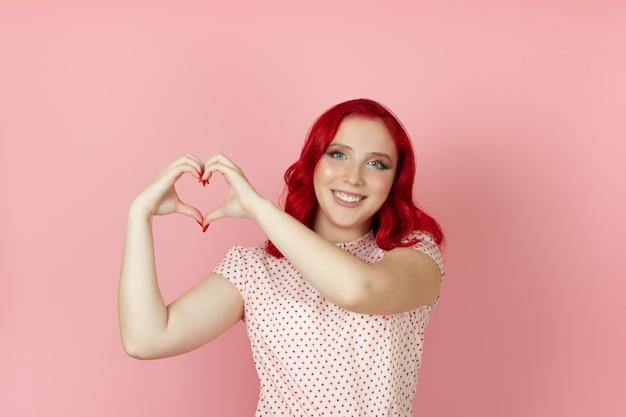 赤い髪の幸せな、笑っている女性のクローズアップは彼女の側で彼女の指からハートサインを作ります
