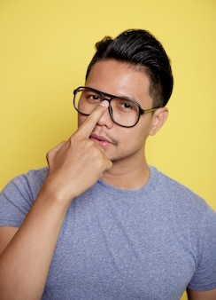黄色の壁に隔離された彼の眼鏡を指しているカジュアルなtシャツを着て幸せな男を閉じます