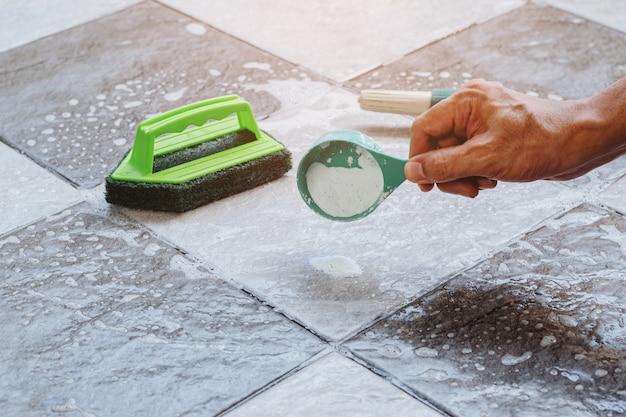 그것을 청소하기 위해 젖은 타일 바닥에 세제를 붓는 사람의 손을 닫습니다.