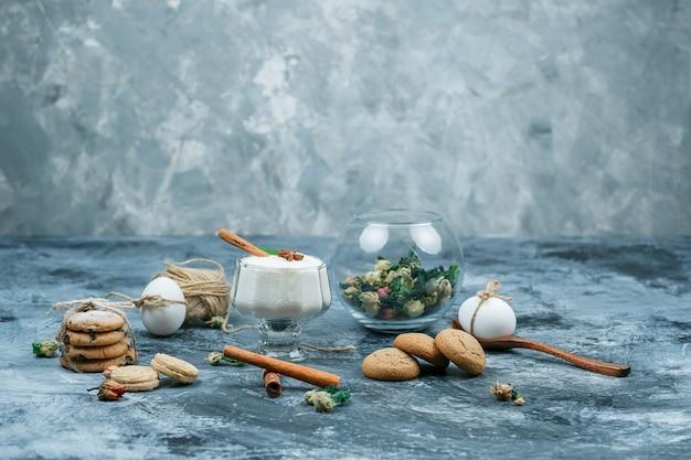 牛乳の水差しとヨーグルトのガラスのボウルをスプーン、クッキー、卵、クルー、シナモン、そして紺と灰色の大理石の表面にある植物でクローズアップします。水平
