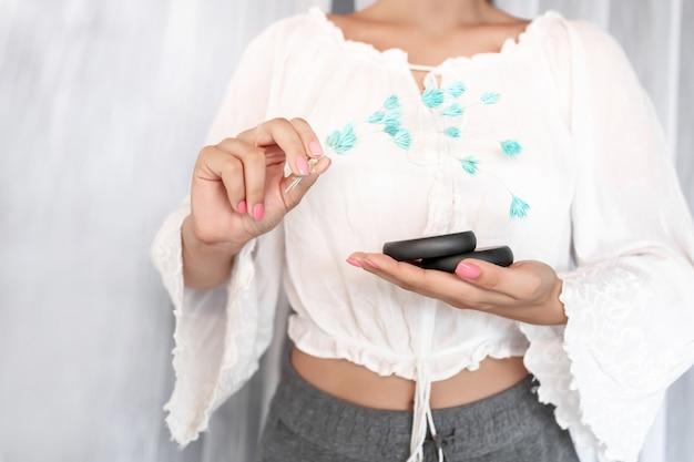 클로즈업 : 아름답고 섬세한 분홍색 매니큐어가있는 흰 블라우스를 입은 여인이 스파 트리트먼트와 파란 꽃을위한 두 개의 검은 돌을 보유하고 있습니다. 스파 및 스킨 케어, 마사지.