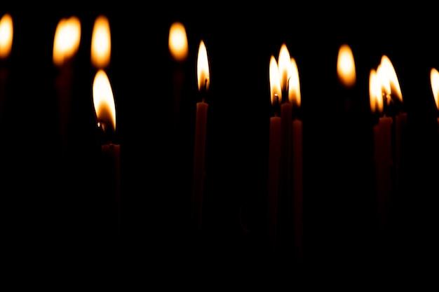 Закройте много горящих свечей, изолированных на черном фоне