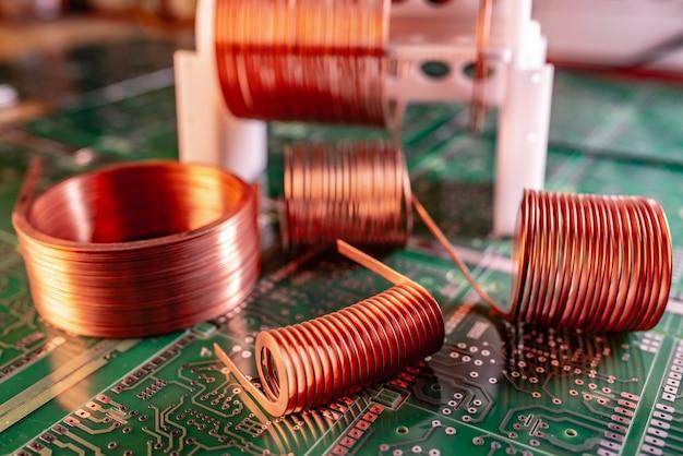 クローズアップ緑色のマイクロサーキットには、ねじれた銅線のかせがたくさん立っています。強力な発振回路と高周波部品を製造するための工場コンセプト