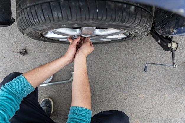 クローズアップ男性が道路上の車のホイールを変更します。