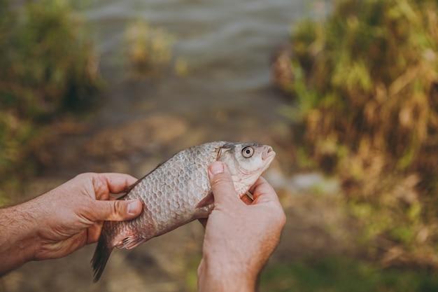 클로즈업 한 남자가 흐릿한 파스텔 호수 배경에 입을 벌린 물고기를 손에 들고 있습니다. 라이프 스타일, 레크리에이션, 어부의 레저 개념. 광고 공간을 복사합니다.