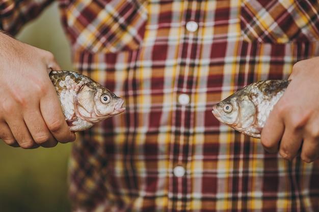 클로즈업 한 남자가 흐릿한 녹색 배경에 키스하는 것처럼 서로 반대편에 입을 벌리고 있는 두 마리의 물고기를 손에 들고 있습니다. 라이프 스타일, 레크리에이션, 어부의 레저 개념. 광고 공간을 복사합니다.