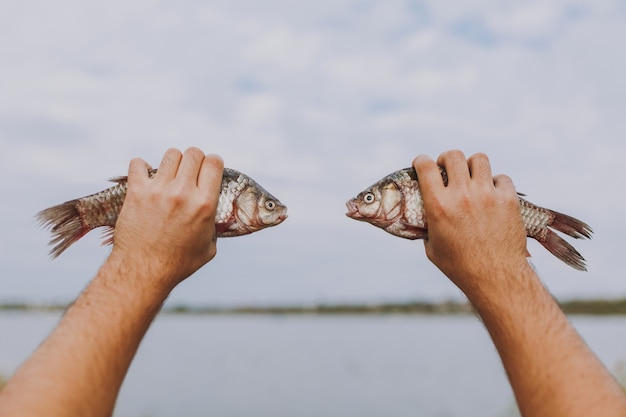 클로즈업 한 남자가 흐릿한 호수와 하늘 배경에서 서로 반대편에 입을 벌리고 있는 두 마리의 물고기를 손에 들고 있습니다. 라이프 스타일, 레크리에이션, 어부의 레저 개념. 광고 공간을 복사합니다.